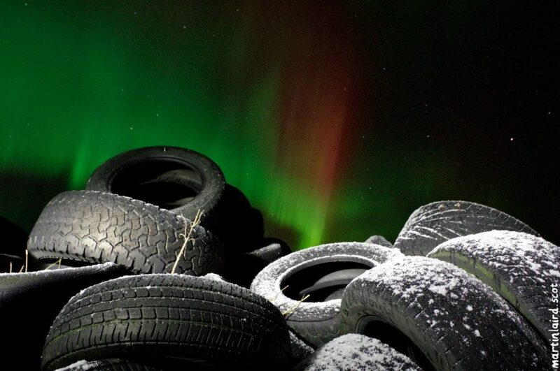 photo of frosty car tires with the aurora borealis behind them, by Martin Scott Laird. Taken in Rendall, Orkney.