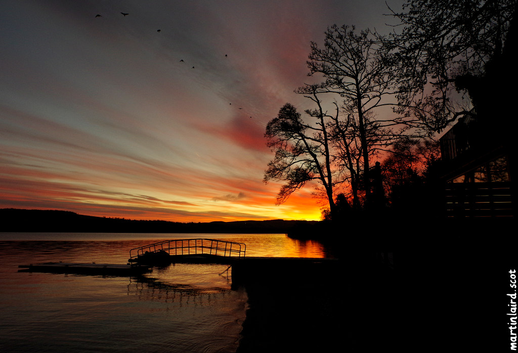 Photo of Loch Lomond at sunrise with a silhouette of trees and a jetty, by Martin Scott Laird, 2017