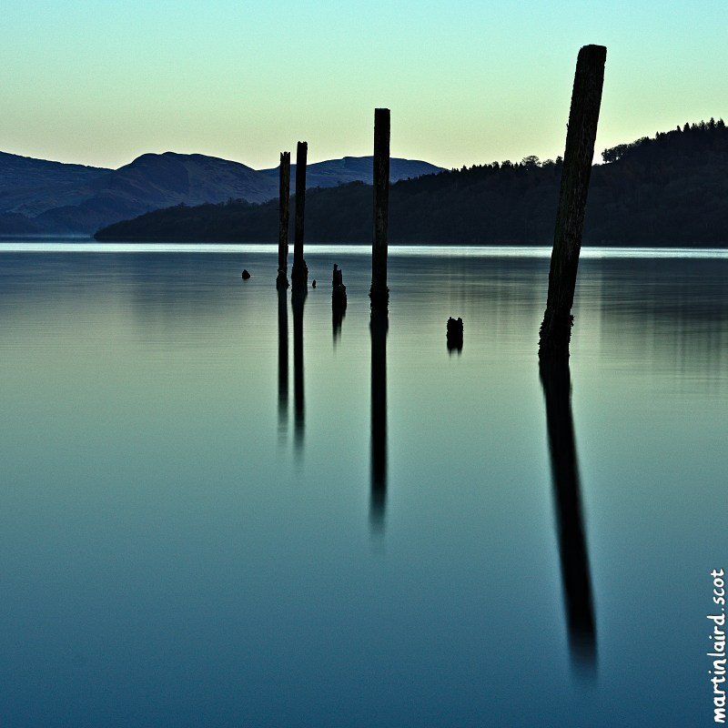 A long exposure photograph of the reflection of wooden piers sticking out of the waters of Loch Lomond, by Martin Scott Laird, 2017