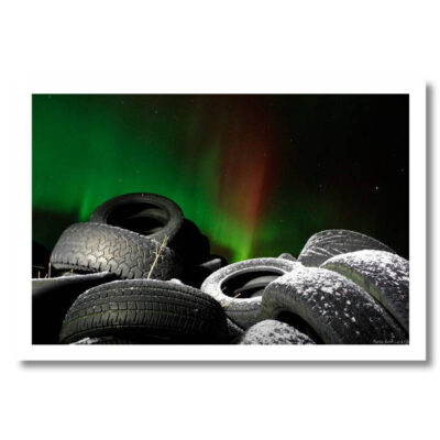 Colour photo of a pile of frosty car tyres lit by a bicycle light. The Northern Lights are strongly in evidence in the sky - bright green and red.