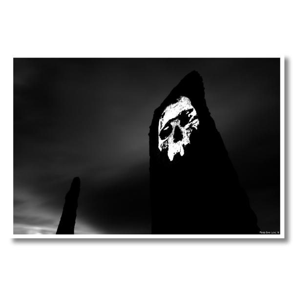 A dark black and white photo of a skull projected onto a standing stone at the Ring of Brodgar, Orkney. Long exposure creates blurred clouds suggesting the passage of time.