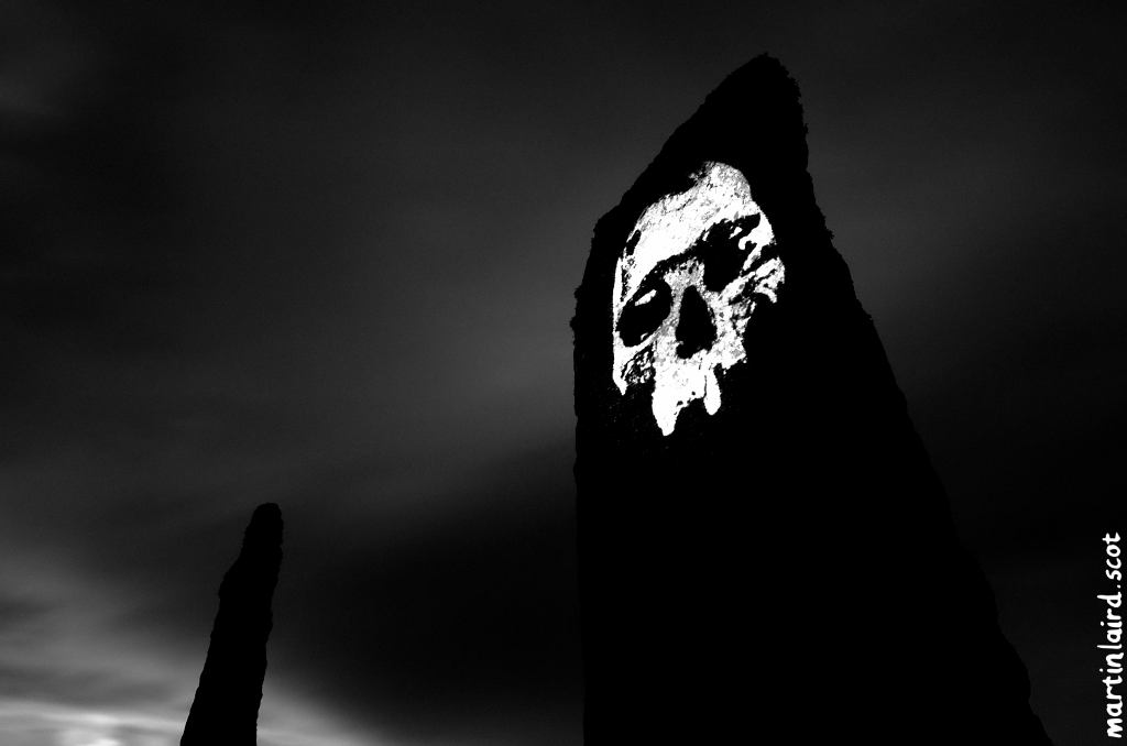 A dark black and white photo of a standing stone at the ring of brodgar with a neolithic skull projected onto it.