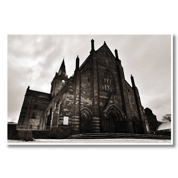 Black and white photo for sale of St Magnus Cathedral in Kirkwall, Orkney. Photo taken on a Winter morning from a low angle, making the Cathedral jagged and imposing.