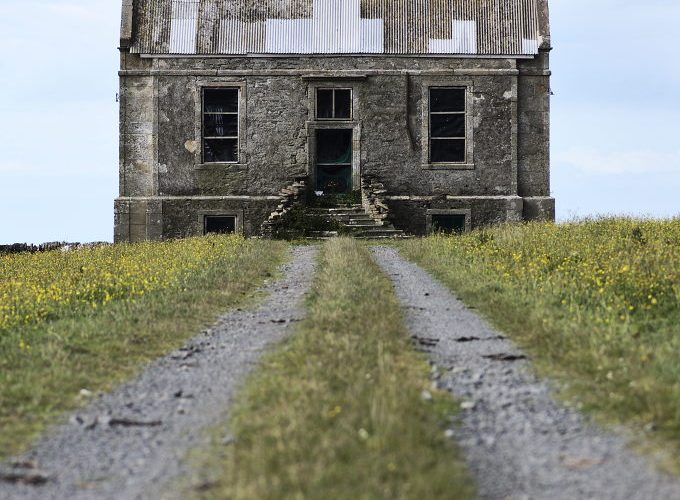 Clestrain Hall, birthplace of John Rae. Distance shot of this derelict building on a clear day with a blurry foreground and slightly desaturated colour.