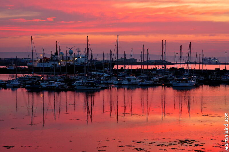 Kirkwall marina, Orkney. Boats silhouetted against the sunset. Very calm, windless, pink & orange sea and sky.