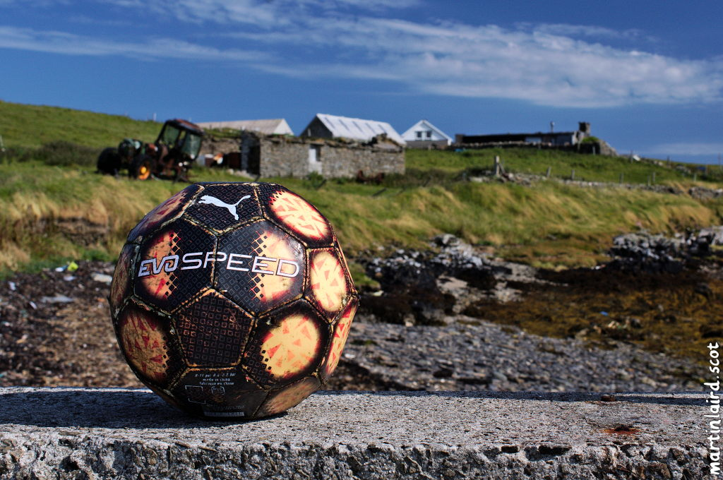 A soft abandoned football sitting on Egilsay pier with a derelict farm and dilapidated tractor in the backrground.