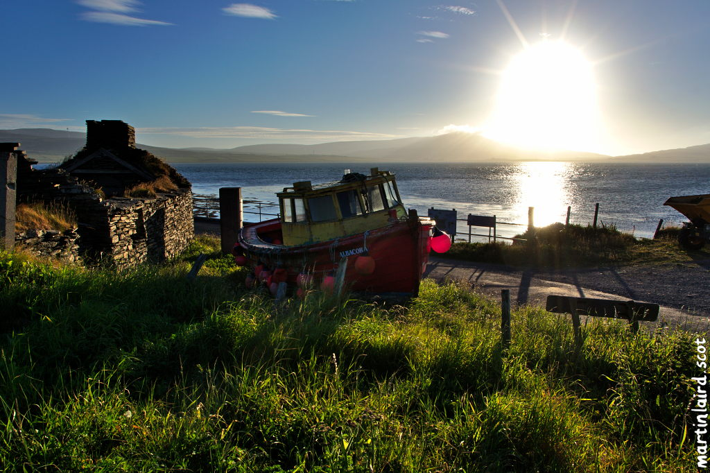 The Albacore, a red boat sitting on the grass near egilsay pier. Bright sun casting its rays between the Rousay hills.