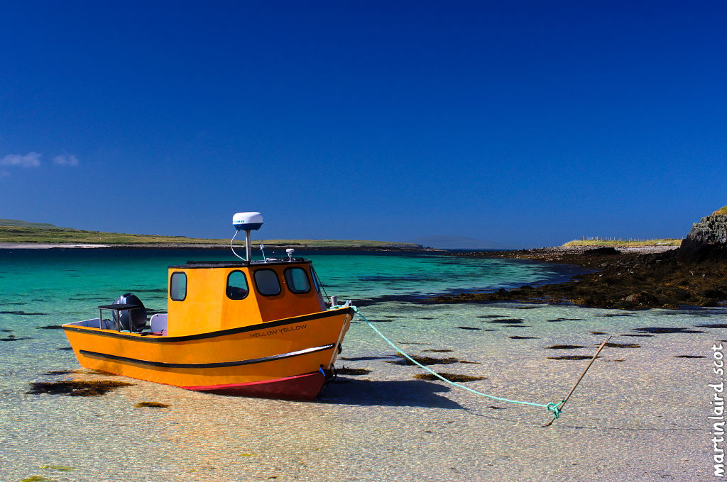 A bright tellow boat called Mellow Yellow moored on the beach, pictured on a sunny day with the vivid blues and greens of the Rousay sound behind.