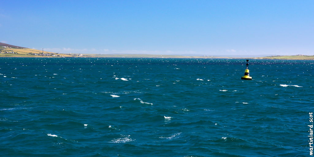 Rousay Sound from the Eynhallow ferry, a vivid blue with choppy white waves standing out and the isles on the horizon