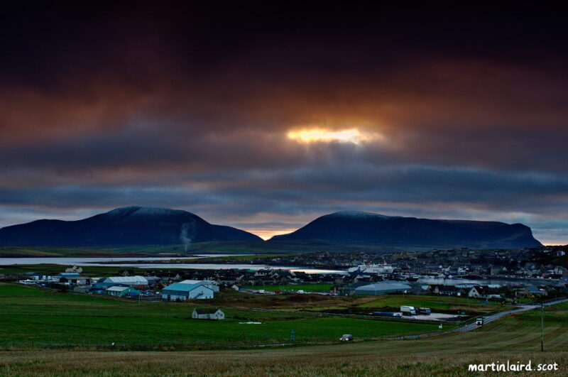 A view of Stromness from Cairston with the setting sun glowing behind a gap inteh clouds behind the hills of Hoy.