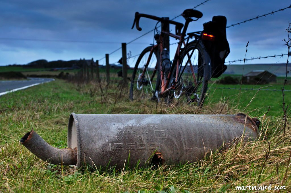 A broken exhaust pipe seen at the side of the road in St. Ola, with a bicycle in the background.