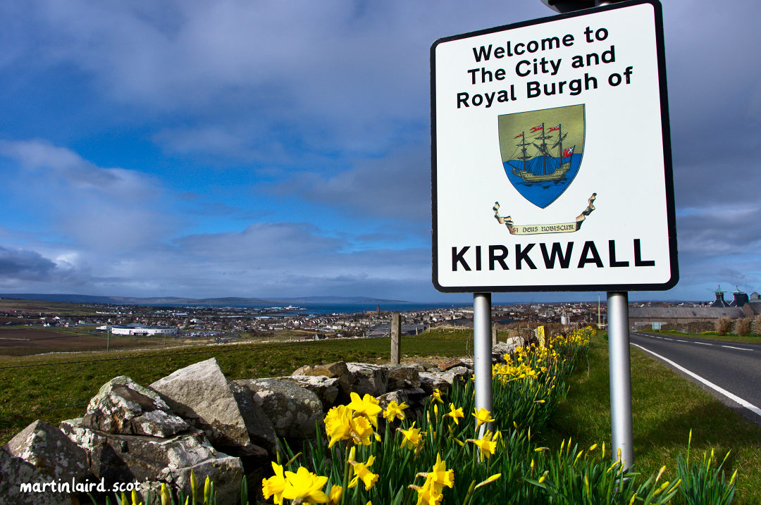 Welcome to the City and Royal Burgh of Kirkwall. Road sign with daffodils overlooking Kirkwall.