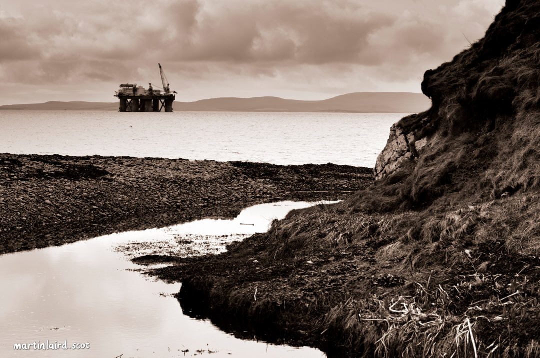 Deepdale Bay on Scapa Flow, Orkney, with an oil rig in the background. Black and white photograph by Martin Laird.