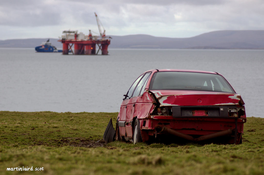 Scapa Flow seen from Deepdale farmland. A wrecked car lies in a muddly field as a warning to bird life. There is an oil rig in the background. Digital photograph by Martin Laird.