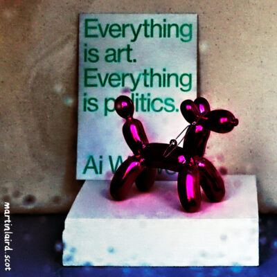 """Everything is art, everything is politics."" Ai Weiwei quote with a Jeff Koons miniature balloon dog in the window of Northlight Gallery, Stromness."